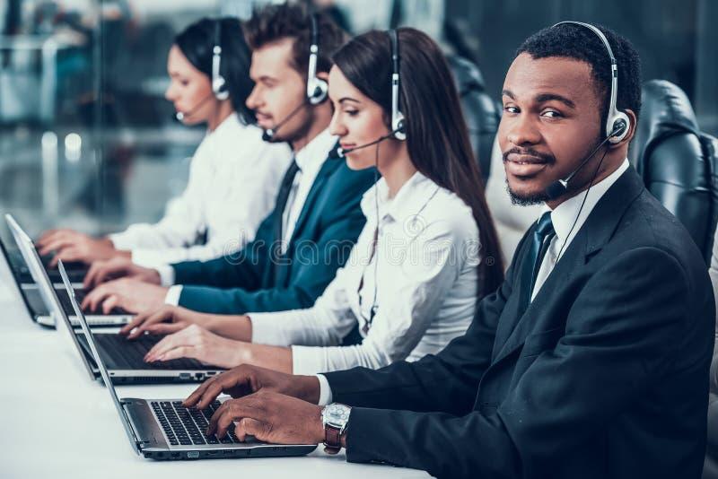 多文化年轻愉快的雇员在电话中心 免版税库存图片