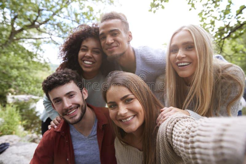 多族群五个年轻成人朋友摆在照相机,当采取selfie在远足时的一个断裂期间 免版税库存图片