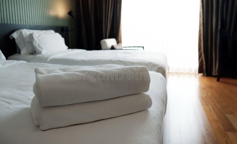 多明戈旅馆客房santo 堆在床上的白色毛巾 在风的帷幕 免版税库存照片