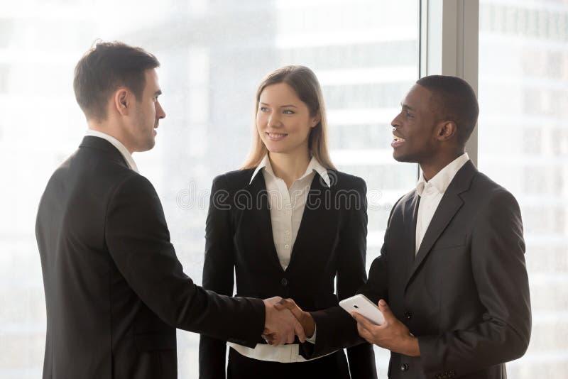 多民族企业家握手在办公室 免版税库存照片
