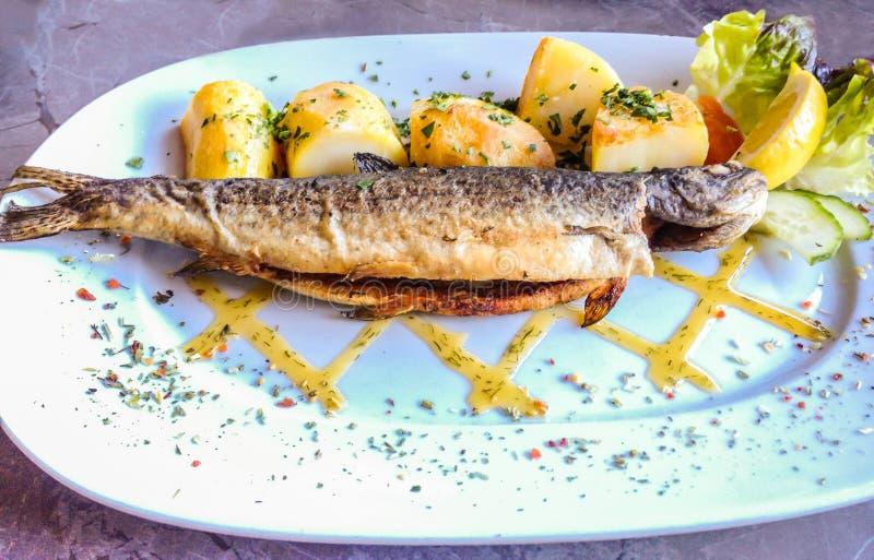 多汁署名自然新鲜的烤鳟鱼用土豆在白色板材烘烤了有大理石桌背景, Hallstatt,奥地利 免版税库存图片