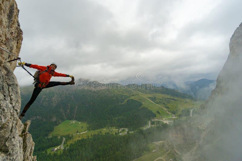 多洛米蒂山Via Ferrata山上的一位迷人的年轻女性登山者,站在疯狂的伸展姿势 图库摄影