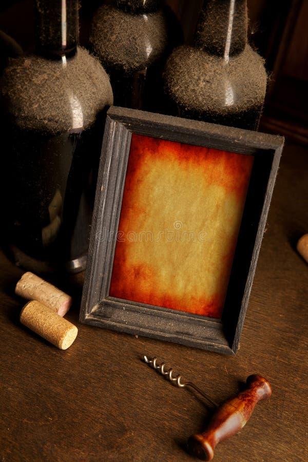 多灰尘的酒瓶、拔塞螺旋和画框 库存照片