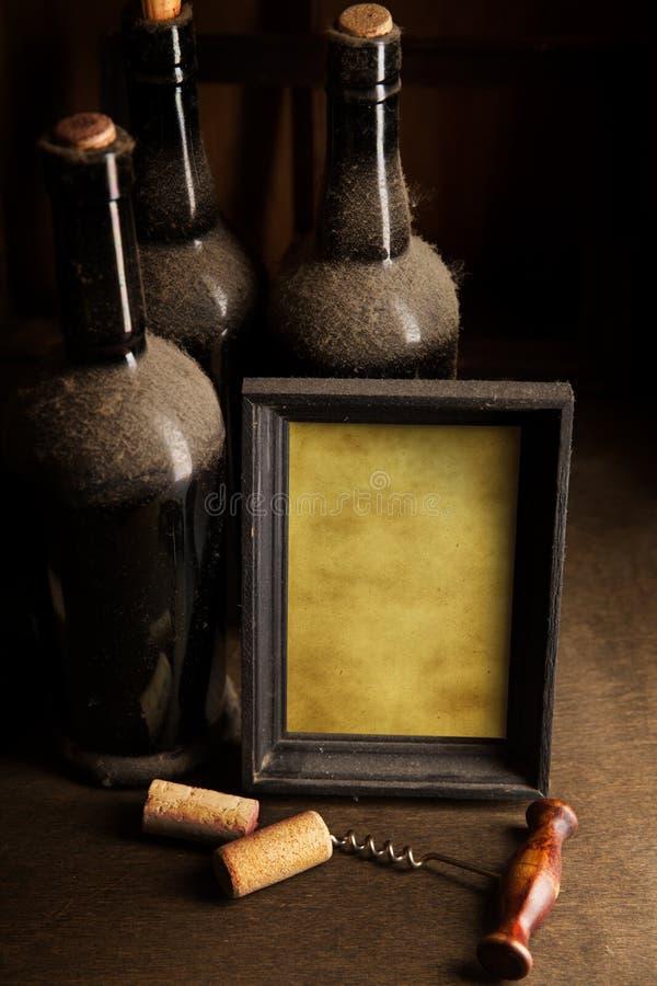 多灰尘的酒瓶和空白的画框 库存图片