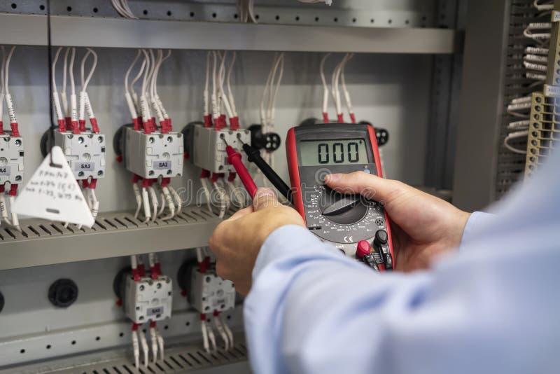 多用电表在电工特写镜头的手上 为在电子箱子的工作服务 电盘区维护  库存照片