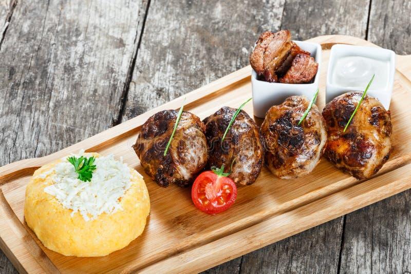 水多的可口肉炸肉排和碎玉米粥或者玉米粥麦片粥用在切板的山羊乳干酪在木背景 免版税库存照片
