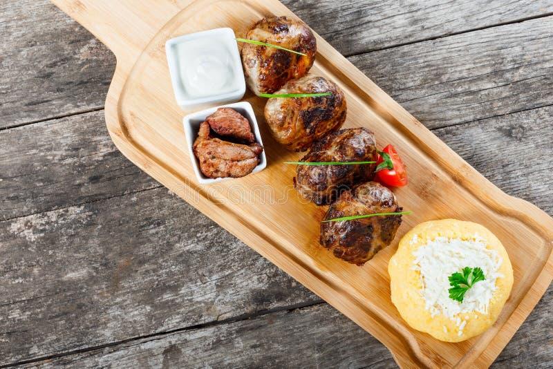 水多的可口肉炸肉排和碎玉米粥或者玉米粥麦片粥用在切板的山羊乳干酪在木背景 图库摄影