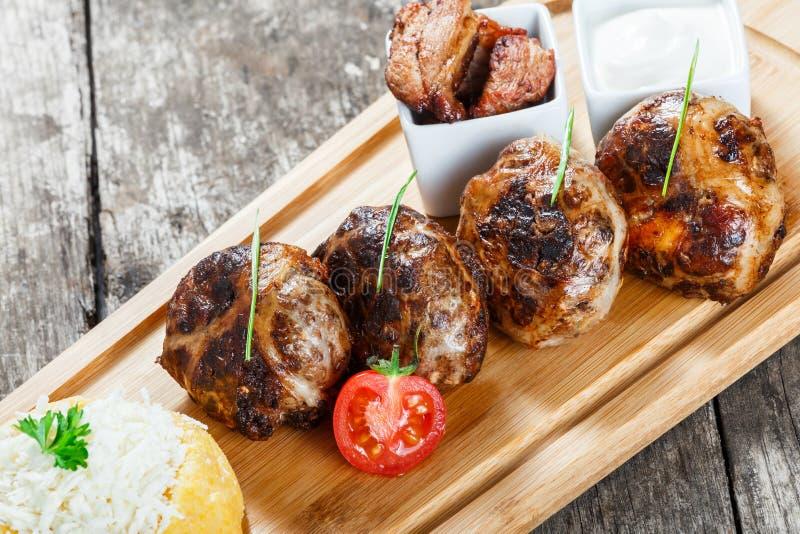 水多的可口肉炸肉排和碎玉米粥,玉米粥麦片粥,用在切板的山羊乳干酪在木背景 库存图片