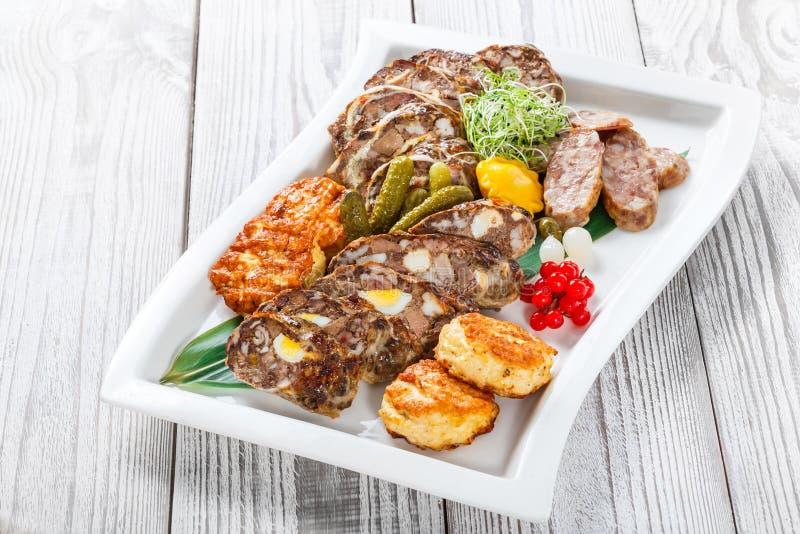 水多的可口肉炸肉排和自创香肠与泡菜在板材在木背景 免版税库存照片