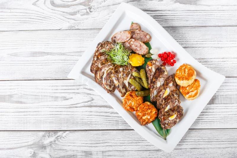 水多的可口肉炸肉排和自创香肠与泡菜在板材在木背景 库存照片