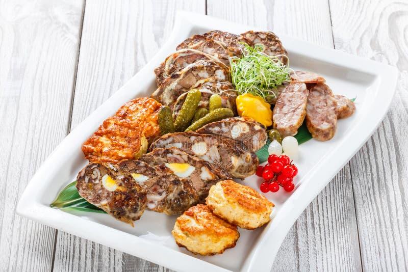 水多的可口肉炸肉排和自创香肠与泡菜在板材在木背景 图库摄影