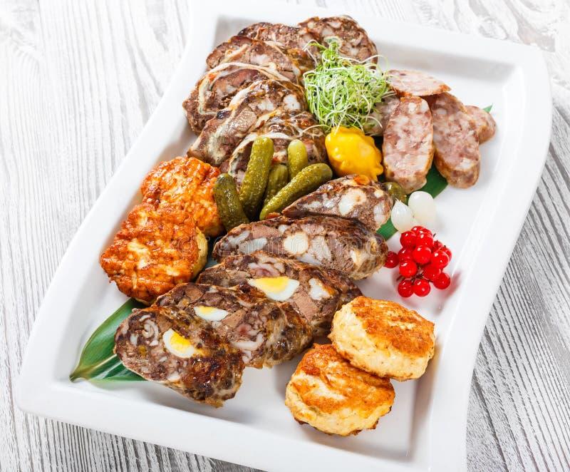 水多的可口肉炸肉排和自创香肠与泡菜在板材在木背景 免版税库存图片