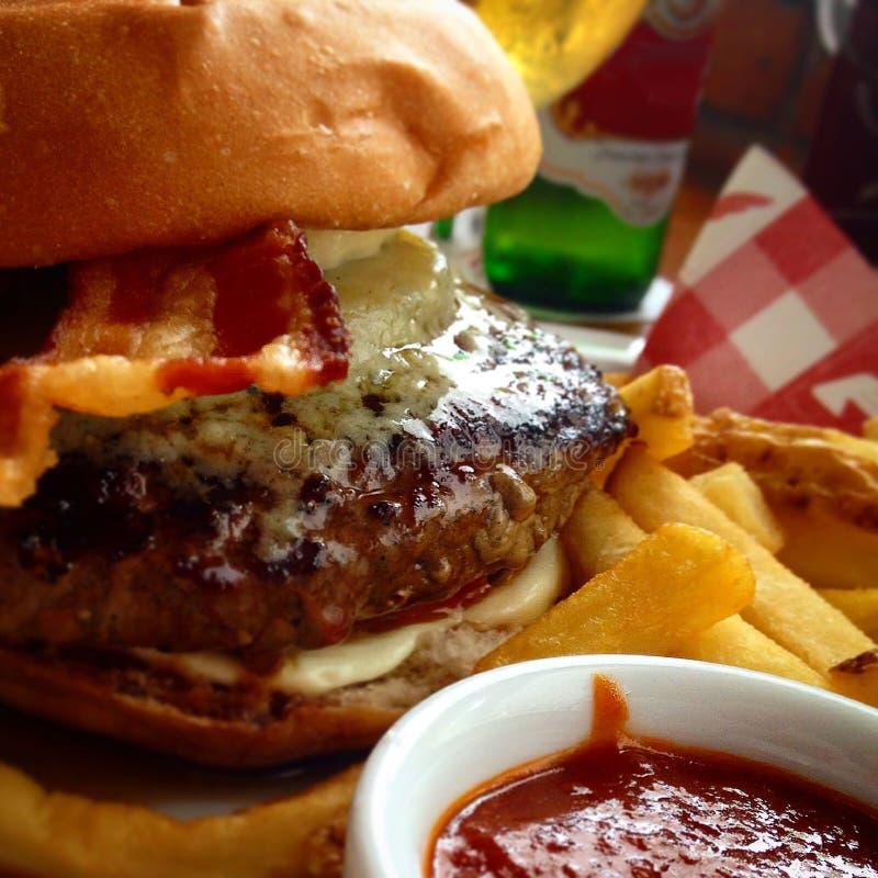 水多的汉堡用戈贡佐拉乳酪、烟肉、油炸物、番茄酱和啤酒 免版税库存照片