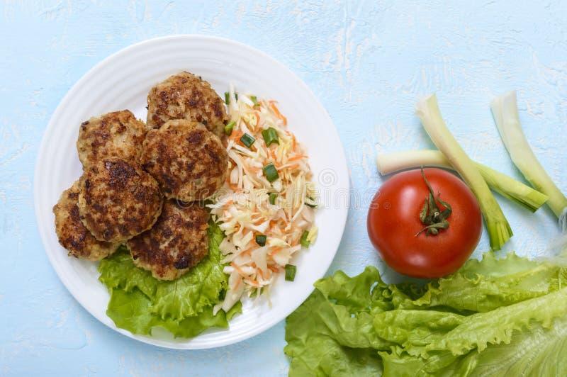 水多的炸肉排和沙拉与新鲜蔬菜:圆白菜,红萝卜,在一块白色板材的绿色 库存照片