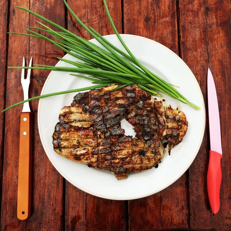 水多的烤肉用在一个碗有刀子的和叉子的葱在一张木桌上 库存图片