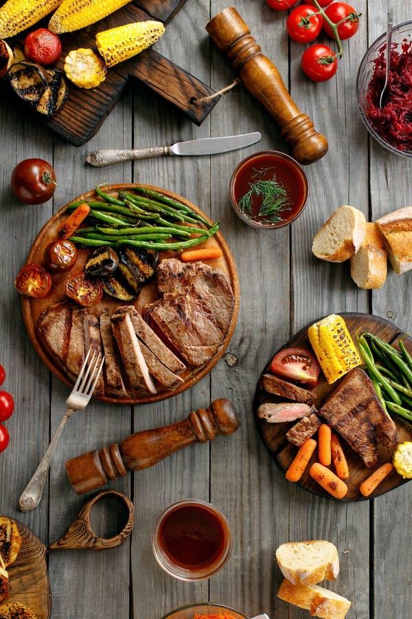 水多的牛排在与烤菜的一个格栅烹调了 免版税库存图片