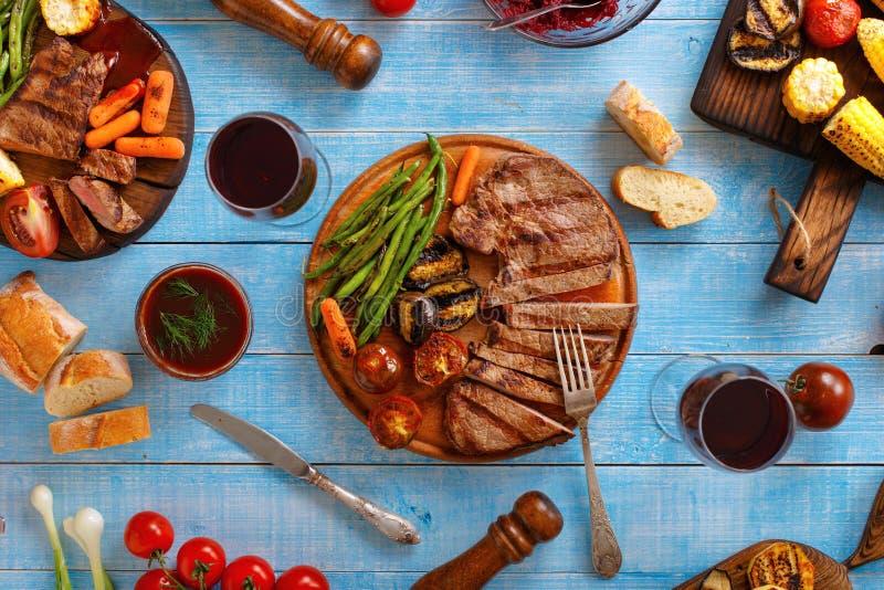 水多的牛排烤了与烤菜和红葡萄酒 免版税库存照片