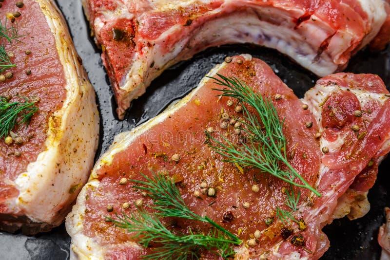 水多的牛排肉用莳萝、胡椒和香料在边,在烹调在烤箱前 免版税库存照片