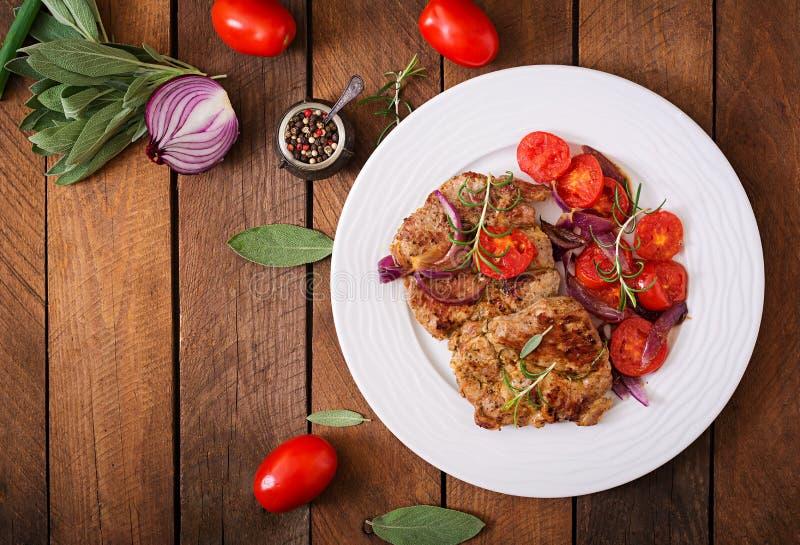 水多的猪肉牛排用迷迭香和蕃茄 免版税图库摄影