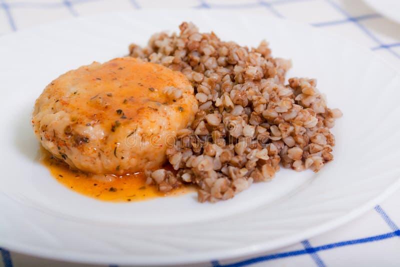 水多的肉炸肉排用西红柿酱用荞麦 免版税库存图片
