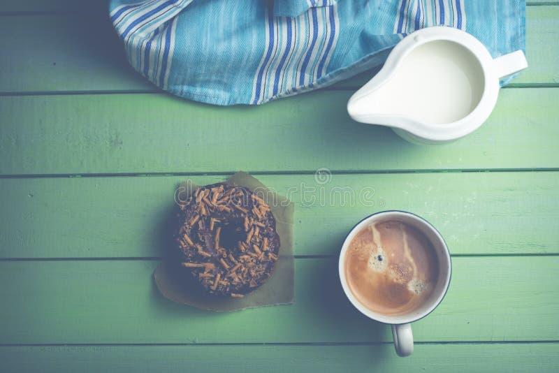 多福饼和咖啡在桌上 免版税库存图片
