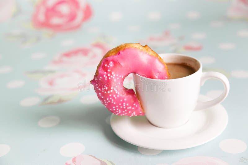 多福饼和咖啡在花卉背景 免版税库存图片
