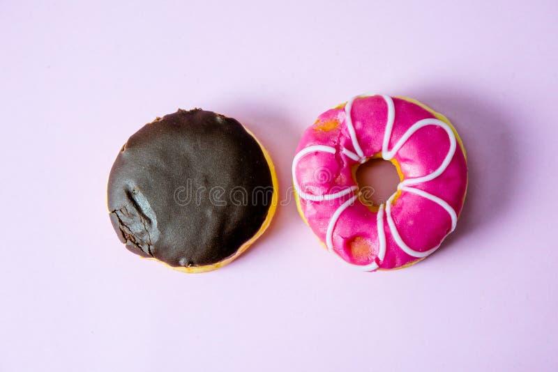 多福饼巧克力和桃红色油炸圈饼盖子用巧克力和sprinkl 库存图片