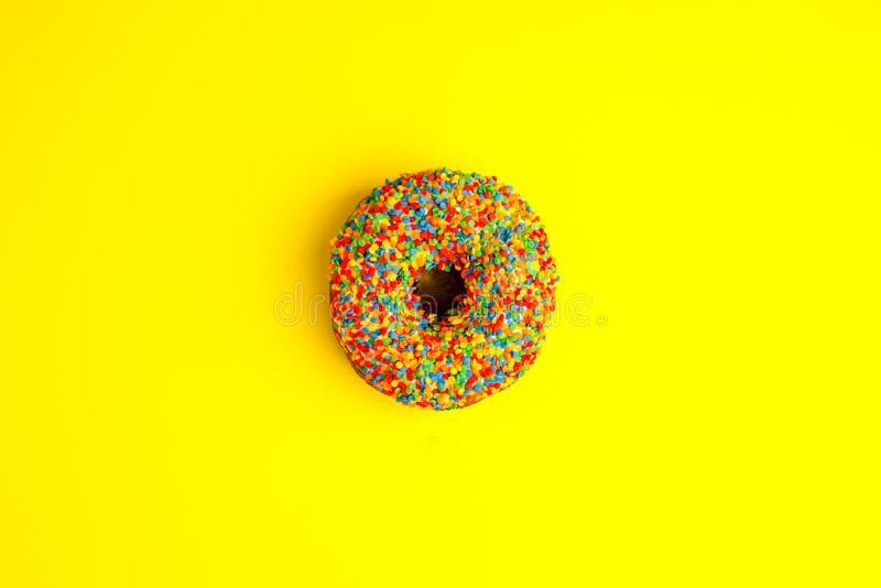多福饼给上釉与在黄色背景洒 现代舱内甲板放置在流行艺术样式的照片样式,党食物 免版税图库摄影