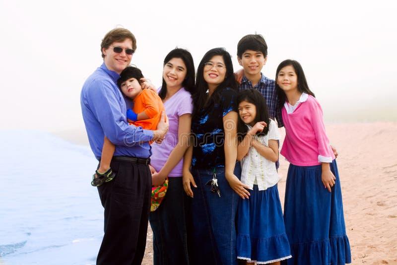 多种族七口之家在有雾的海滩 库存图片