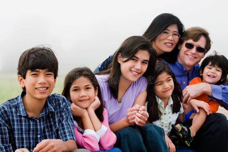 多种族七口之家坐海滩 免版税库存照片