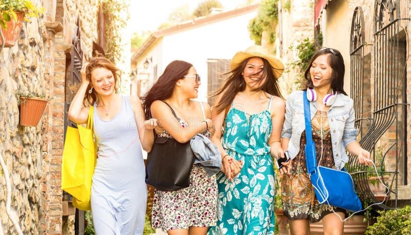 多种族千福年的女朋友走和谈话在老镇游览-愉快的女孩获得乐趣在城市街道附近 库存照片