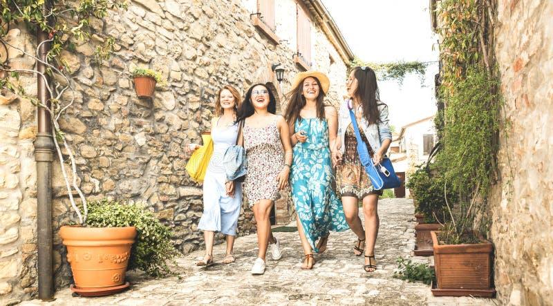 多种族千福年的女朋友走在老镇游览的-愉快的女孩最好的朋友获得乐趣在城市街道附近-大学 库存图片