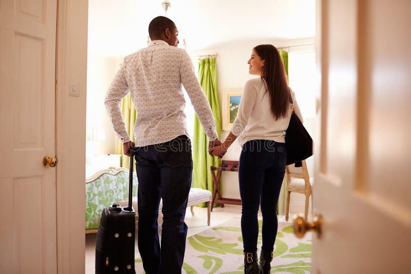 年轻多种族夫妇进来到旅馆客房,后面看法 库存图片