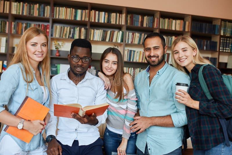 多种族学生获得乐趣在图书馆,当为检查做准备时 免版税库存照片