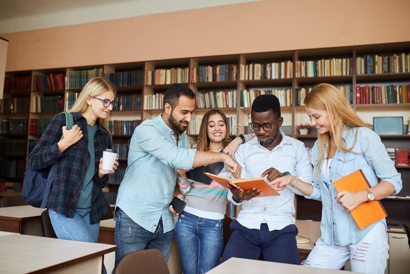 多种族学生获得乐趣在图书馆,当为检查做准备时 免版税库存图片