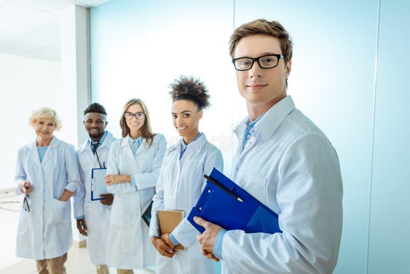 多种族小组微笑的实习生在实验室用剪贴板连续涂身分 免版税库存图片