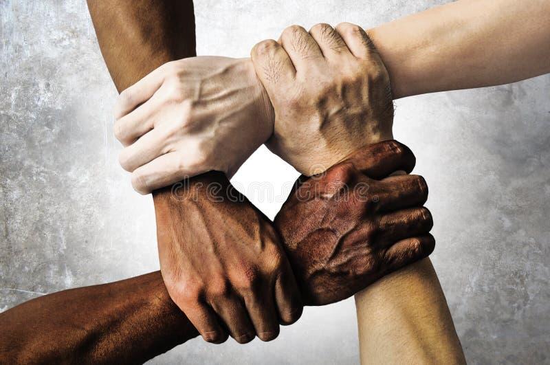 多种族小组用举行的黑非裔美国人的白种人和亚洲手在容忍团结爱的腕子和反 库存照片