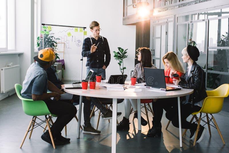 多种族年轻创造性的人在现代办公室与膝上型计算机,片剂,智能手机,笔记本一起工作 图库摄影