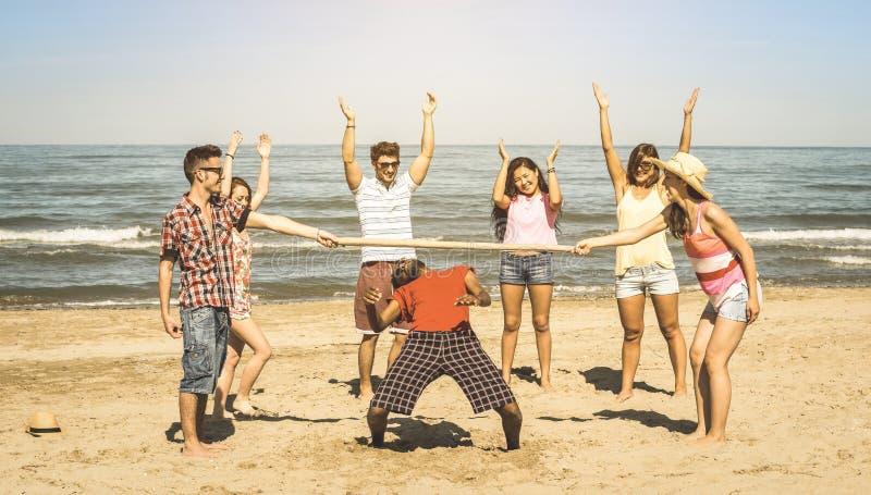 多种族愉快的朋友编组获得与中间状态的乐趣在海滩 库存照片