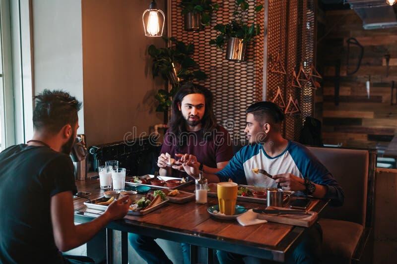 多种族朋友吃在咖啡馆的早餐 年轻人聊天,当有鲜美食物和饮料时 一起人住处 免版税图库摄影
