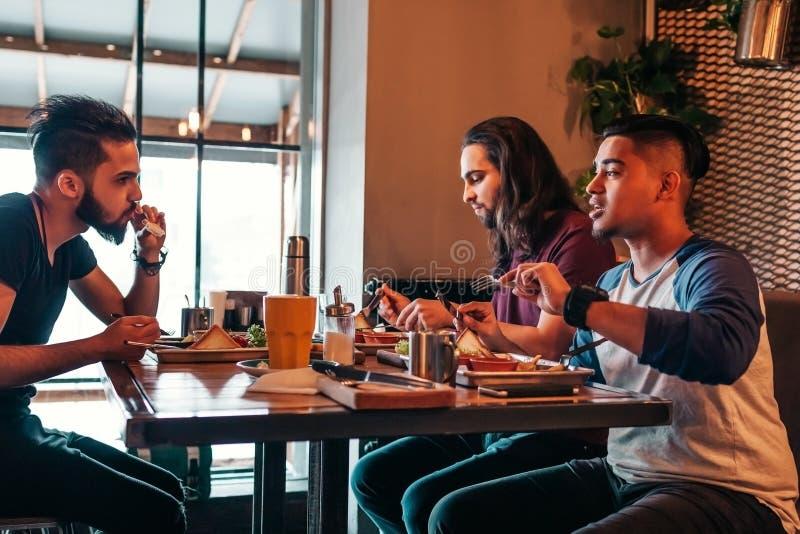 多种族朋友吃在咖啡馆的早餐 年轻人聊天,当有鲜美食物和饮料时 一起人住处 库存图片