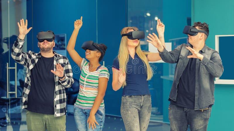 多种族朋友编组使用在vr玻璃户内 与获得的年轻人的虚拟现实概念乐趣一起 免版税库存照片