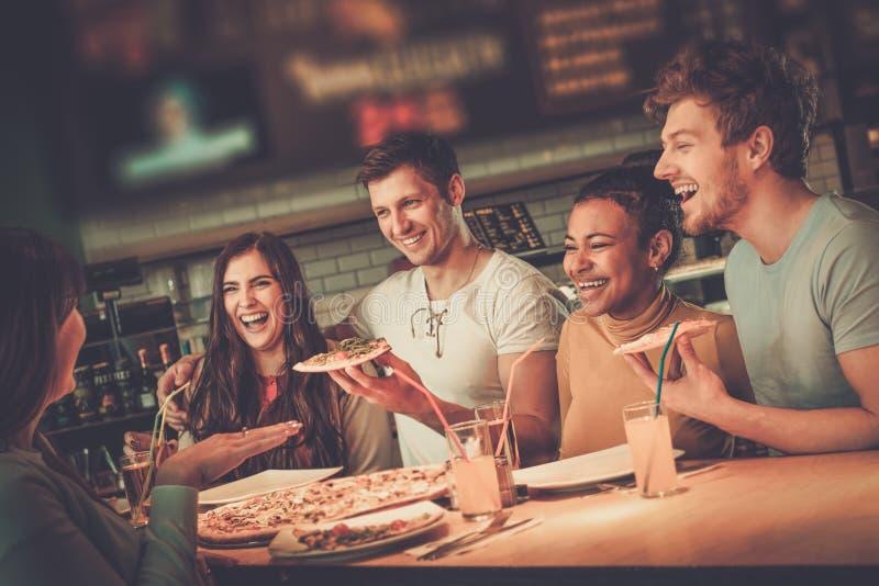 多种族朋友获得吃的乐趣在比萨店 免版税图库摄影
