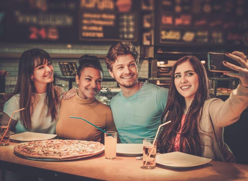 多种族朋友获得吃的乐趣在比萨店 图库摄影