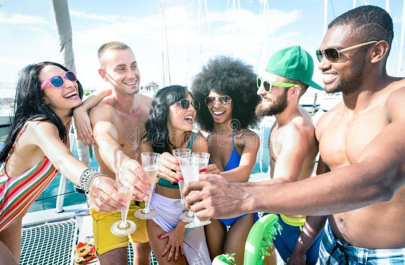 多种族朋友饮用乐趣饮用的香槟酒在帆船党-与年轻多种族人民的友谊概念 免版税库存照片