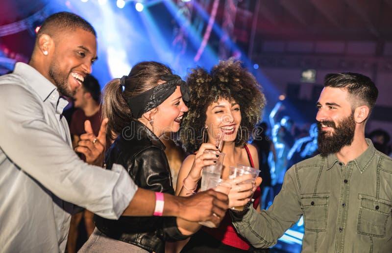 多种族年轻朋友跳舞在夜总会的-愉快的人民 免版税库存图片