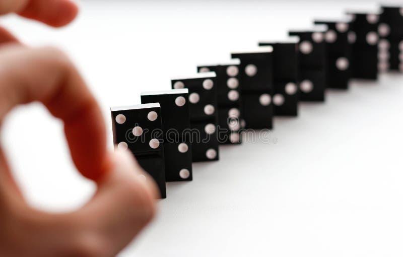 多米诺敲手指的轻打 在丝毫隔绝的多米诺 库存照片