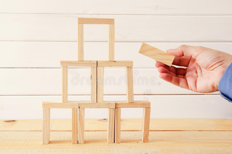从多米诺木块的男性手大厦塔 免版税库存照片