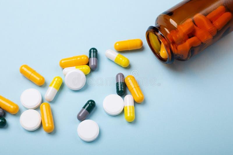 多色片剂和药片胶囊从玻璃瓶在蓝色背景特写镜头 库存图片
