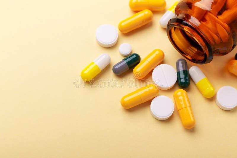 多色片剂和药片胶囊从玻璃瓶在黄色背景特写镜头 免版税库存照片